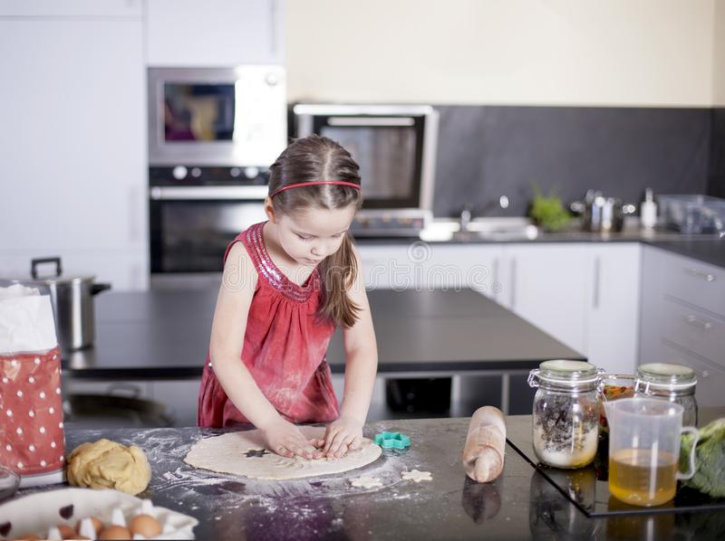 Little cute girl is learning how to make cake, in kitchen, Family concept stock photos