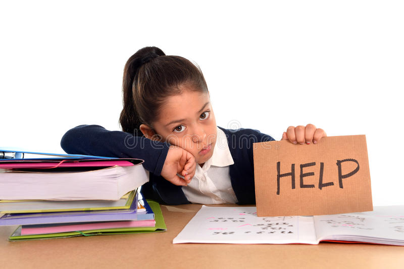 Sweet little girl bored under stress asking for help in hate school concept. Sweet little female latin child studying on desk lasking for help in stress with a stock images