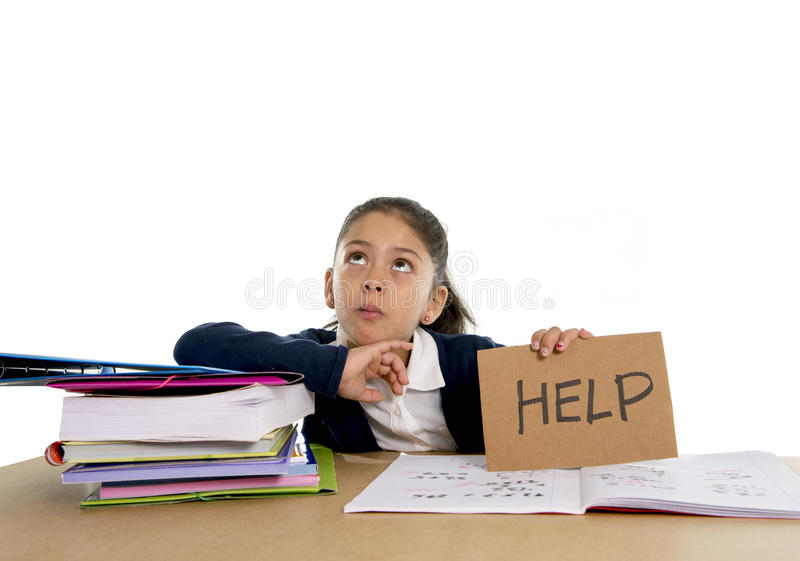 Sweet little girl bored under stress asking for help in hate school concept. Sweet little female latin child studying on desk asking for help in stress with a stock photography