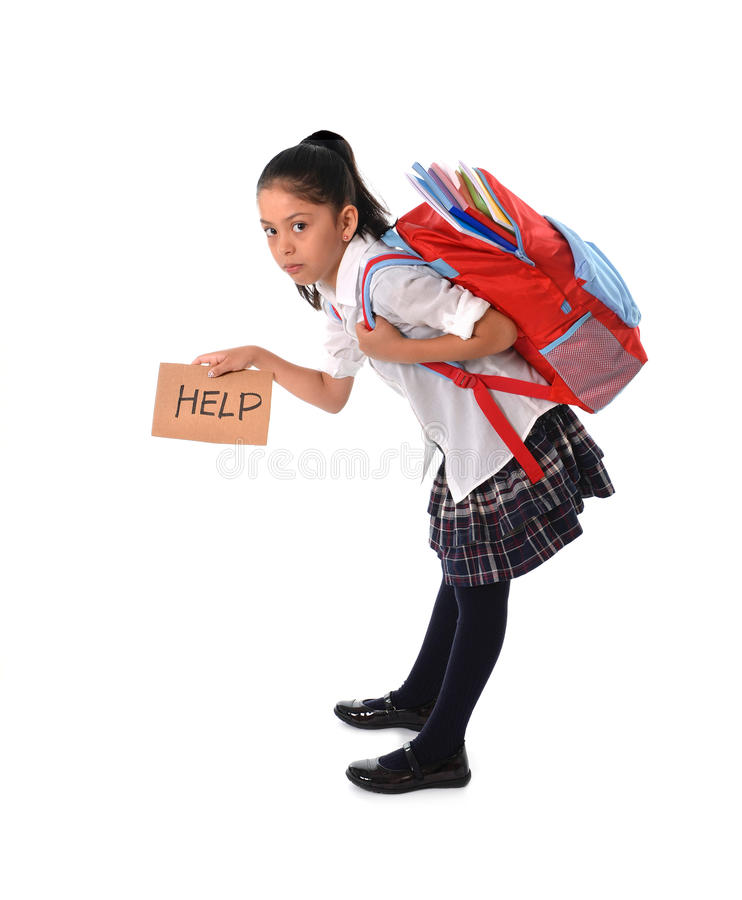 Sweet little girl carrying very heavy backpack or schoolbag full of school material stock images