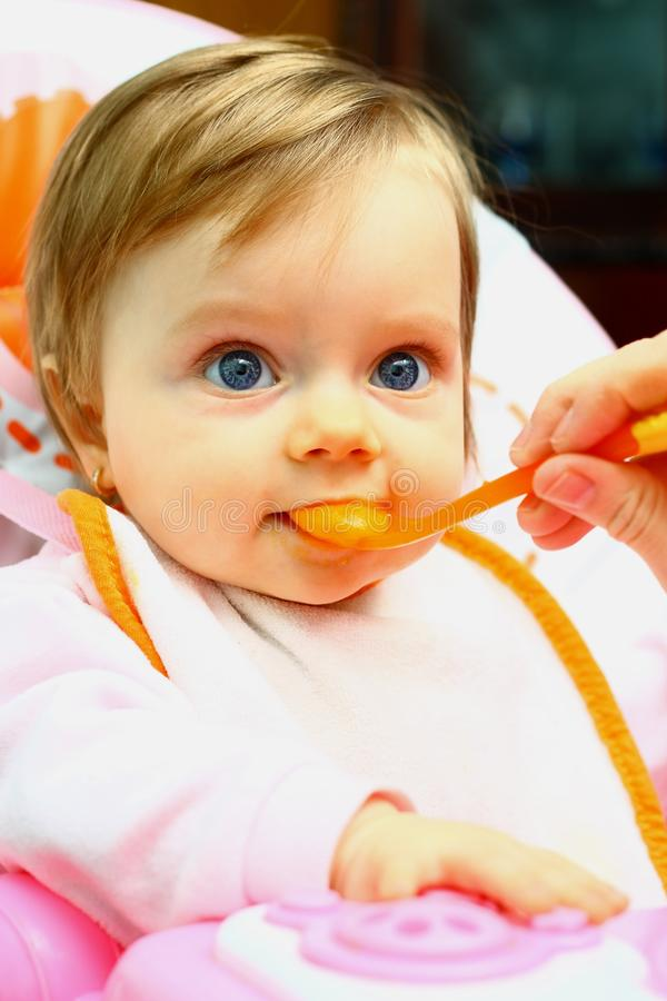 Sweet little girl eating with spoon royalty free stock images