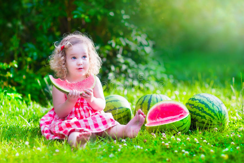 Sweet little girl eating watermelon. Child eating watermelon in the garden. Kids eat fruit outdoors. Healthy snack for children. Little girl playing in the stock images
