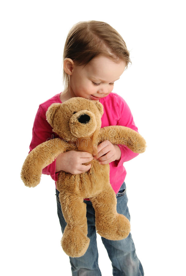 Sweet little girl holding a teddy bear royalty free stock image