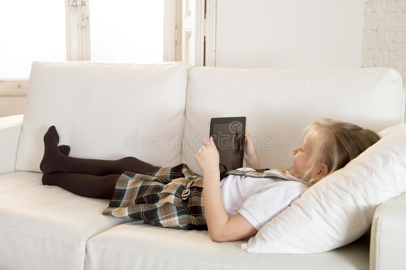 Sweet little girl lying on home sofa couch using internet app on digital tablet pad. Sweet cute and beautiful 6 or 7 years old female child with blond hair in royalty free stock photography