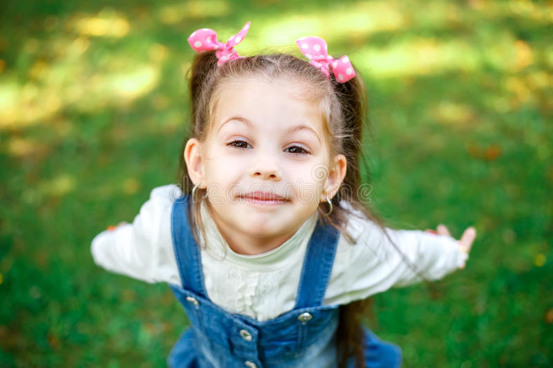 Sweet little girl outdoors with curly hair in two long tails, closeup portret. stock images