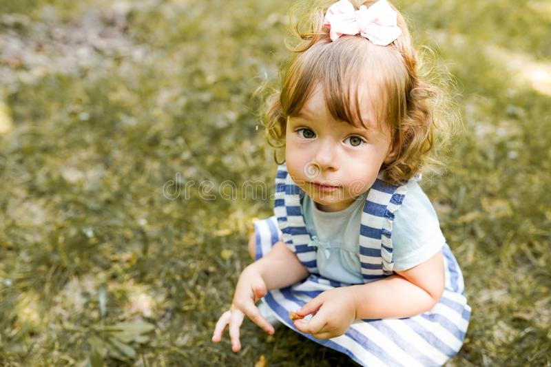 Sweet little girl outdoors with curly hair walking in the park, copy space stock photography