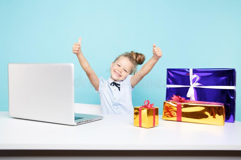 Sweet little girl siting at the desk with a lot of xmas gifts and the laptop. royalty free stock photos