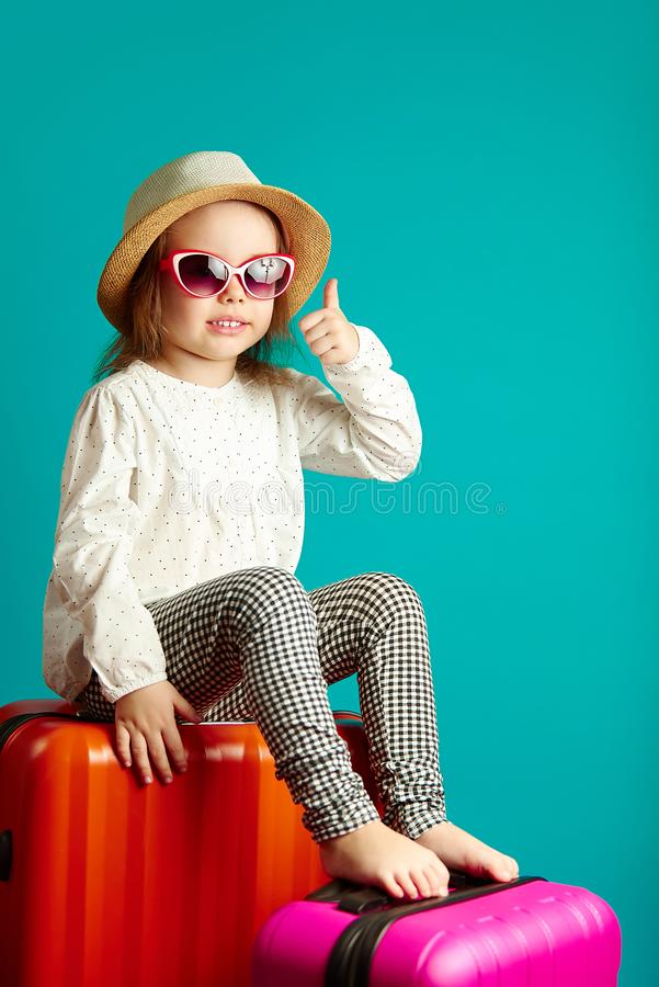 Sweet little girl sits on suitcases, waiting for trip, portrait of happy child on isolated blue. royalty free stock photography