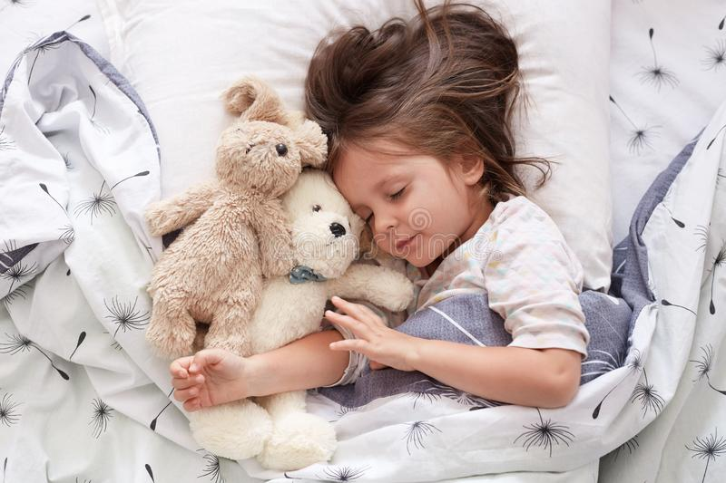 Sweet little girl sleeping with toys in crib. Close up portrait of infant sleeping in cot. Beautiful toddler sleeping with toy stock photo