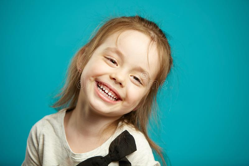 Sweet little girl smiling on blue isolated background. stock photos