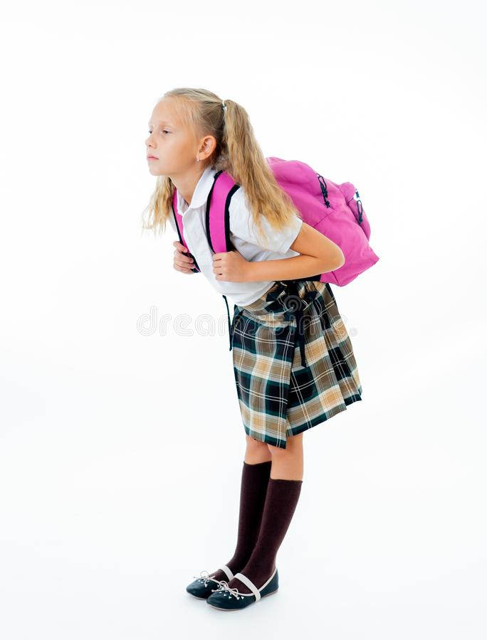Sweet little girl in uniform carrying heavy big pink backpack or school bag full causing stress and pain on back due to overweight. Isolated on white background royalty free stock photo