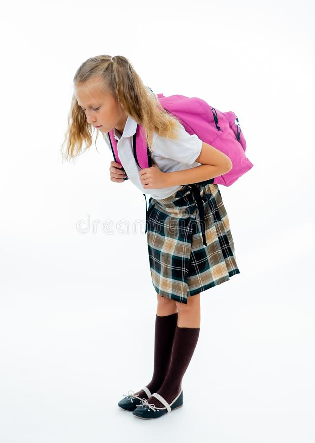Sweet little girl in uniform carrying heavy big pink backpack or school bag full causing stress and pain on back due to overweight. Isolated on white background royalty free stock image
