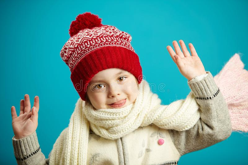 Sweet little girl in winter hat and scarf, raised hands up, head leaned sideways, has a cute and charming face, stands royalty free stock image
