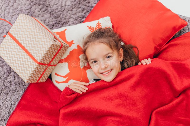 Sweet little kid woke up in the morning with Christmas gift on her side. stock photo