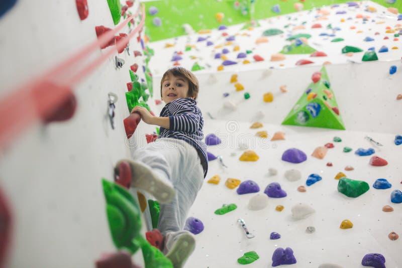 Sweet little preschool boy, climbing wall indoors stock images