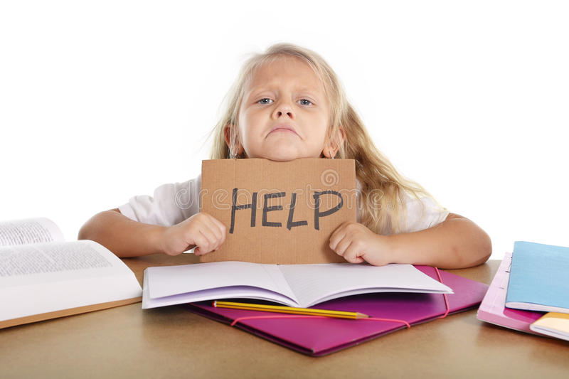 Sweet little school girl holding help sign in stress with books and homework. Sweet little blonde hair school girl holding help sign in stress with books and royalty free stock photo