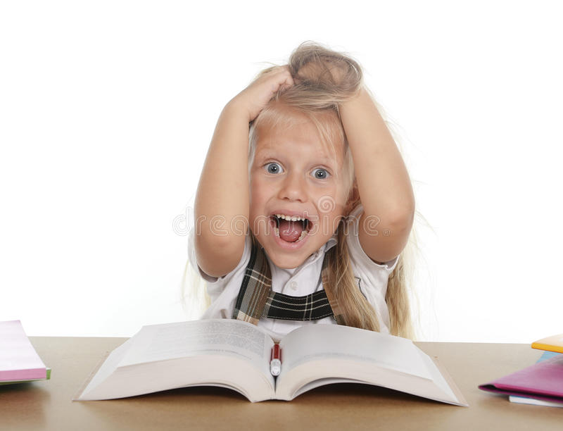 Sweet little school girl pulling her blonde hair in stress getting crazy while studying. And doing homework in children education concept isolated on white royalty free stock images