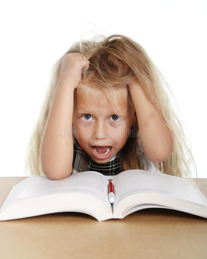 Sweet little school girl pulling her blonde hair in stress getting crazy while studying. And doing homework in children education concept isolated on white royalty free stock photo