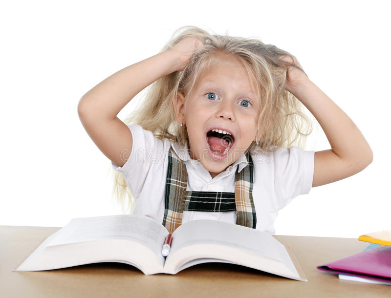 Sweet little school girl pulling her blonde hair in stress getting crazy while studying. And doing homework in children education concept isolated on white royalty free stock photography