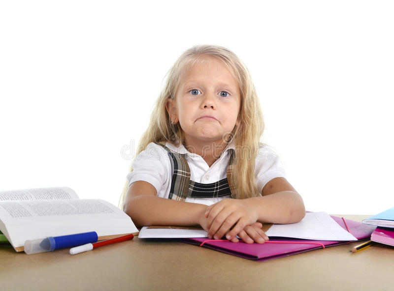 Sweet little school girl tired and sad in stress with books and homework. Sweet little blonde hair school girl looking bored and tired in stress with books and stock photography
