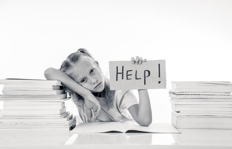 Sweet little schoolgirl feeling exhausted and stress by load of homework and schoolwork. Angry little girl with a negative attitude towards studies and school royalty free stock photos
