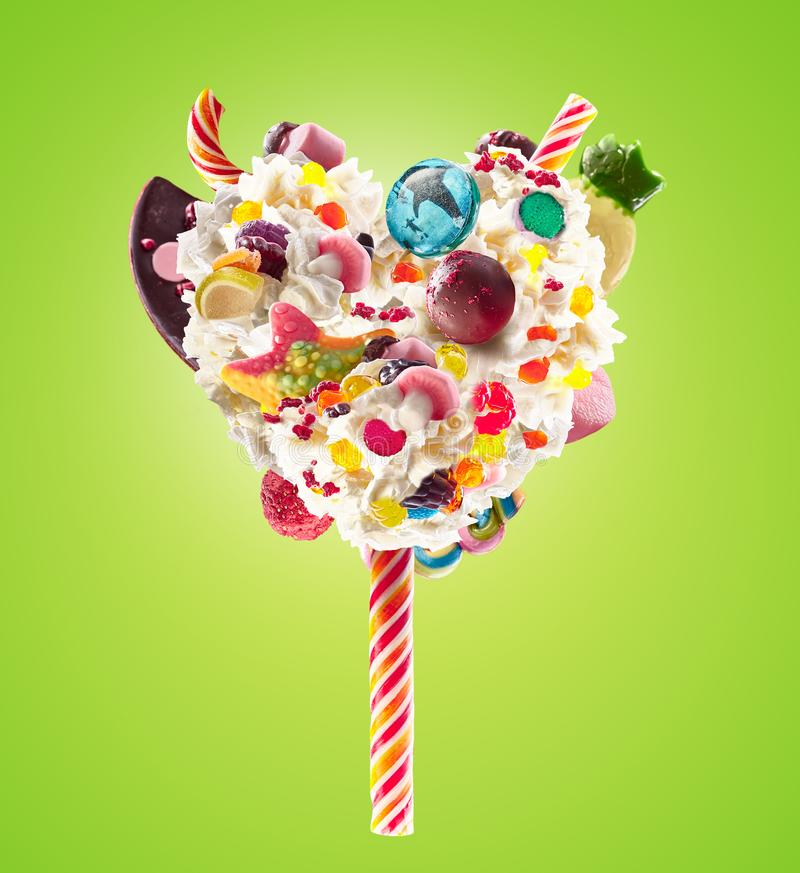 Sweet Lolipop in Heart form of whipped cream with sweets, jellies, heart front view. Crazy freakshake food trend. Front. View of whipped heart of cream lolly stock photography