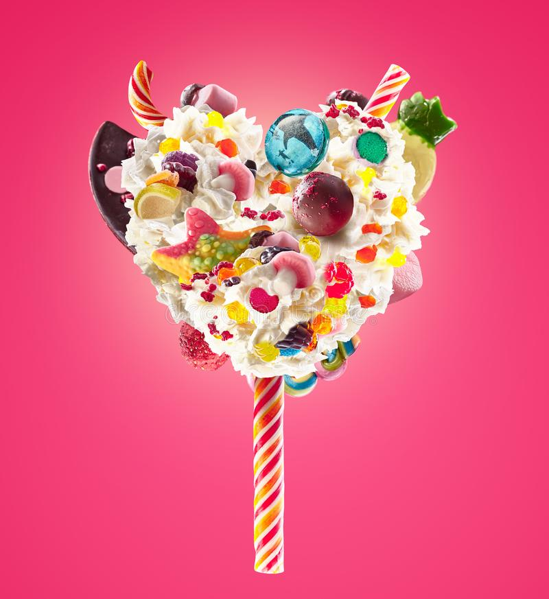 Sweet Lolipop in Heart form of whipped cream with sweets, jellies, heart front view. Crazy freakshake food trend. Front. View of whipped heart of cream lolly stock images