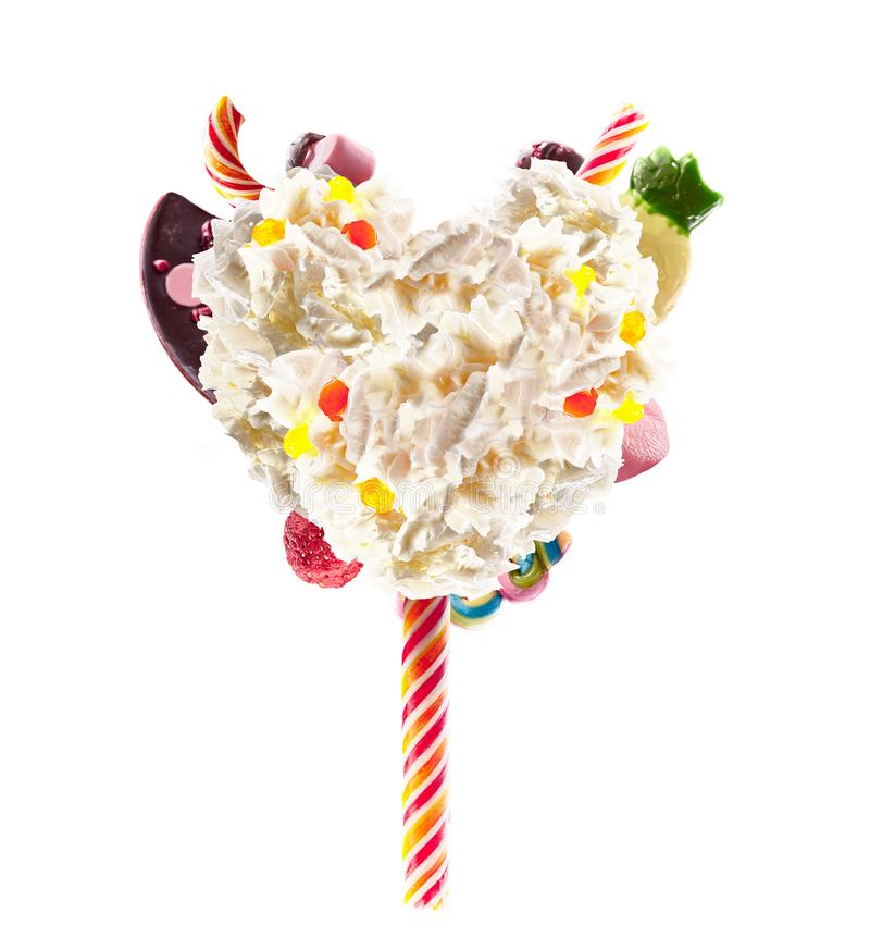 Sweet Lolipop in Heart form of whipped cream with sweets, jellies, heart front view. Crazy freakshake food trend. Front royalty free stock images