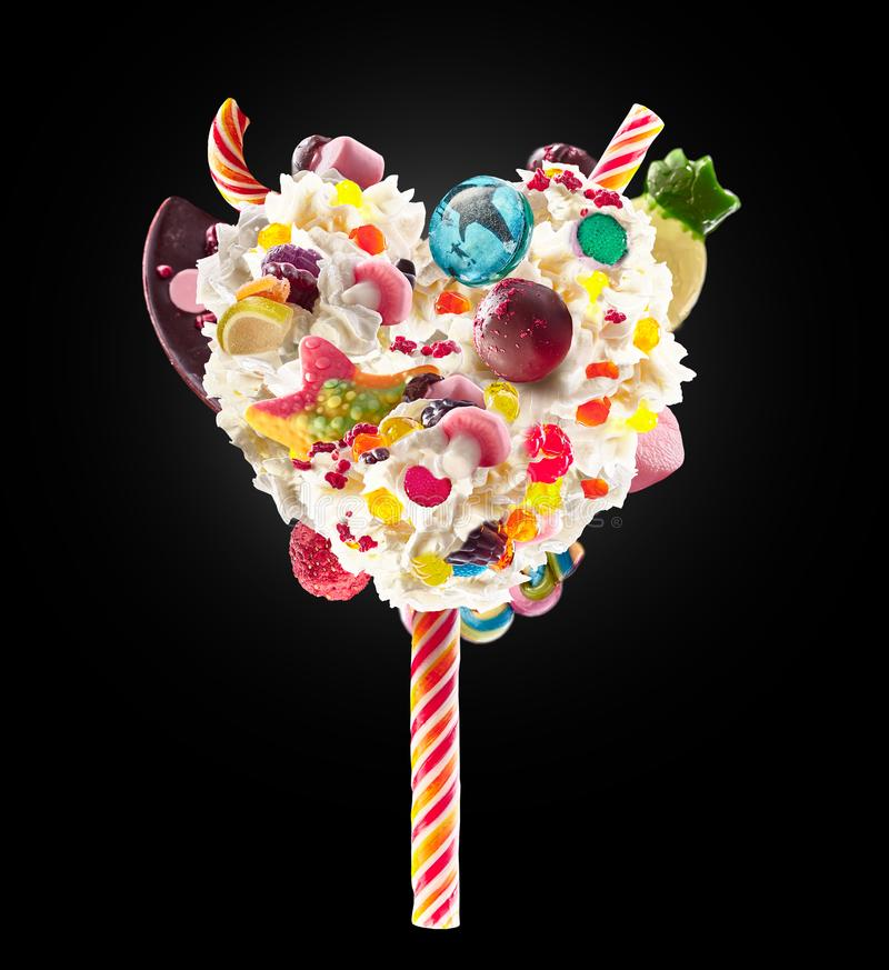 Sweet Lolipop in Heart form of whipped cream with sweets, jellies, heart front view. Crazy freakshake food trend. Front stock photo