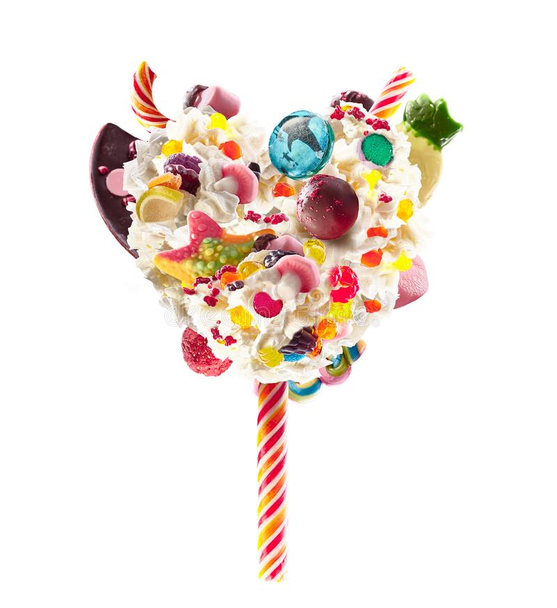 Sweet Lolipop in Heart form of whipped cream with sweets, jellies, heart front view. Crazy freakshake food trend. Front stock photos