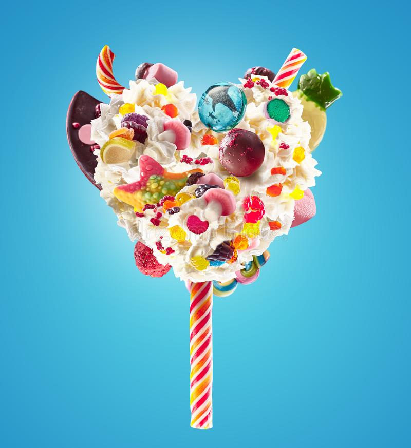 Sweet Lolipop in Heart form of whipped cream with sweets, jellies, heart front view. Crazy freakshake food trend. Front. View of whipped heart of cream lolly royalty free stock image