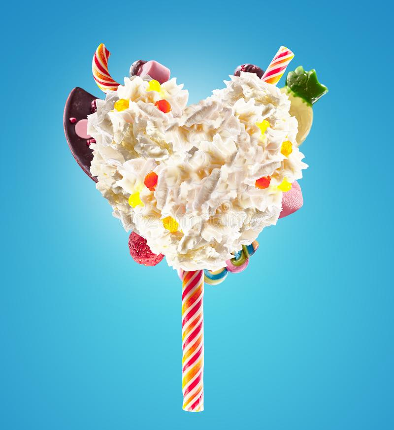 Sweet Lolipop in Heart form of whipped cream with sweets, jellies, heart front view. Crazy freakshake food trend. Front royalty free stock image