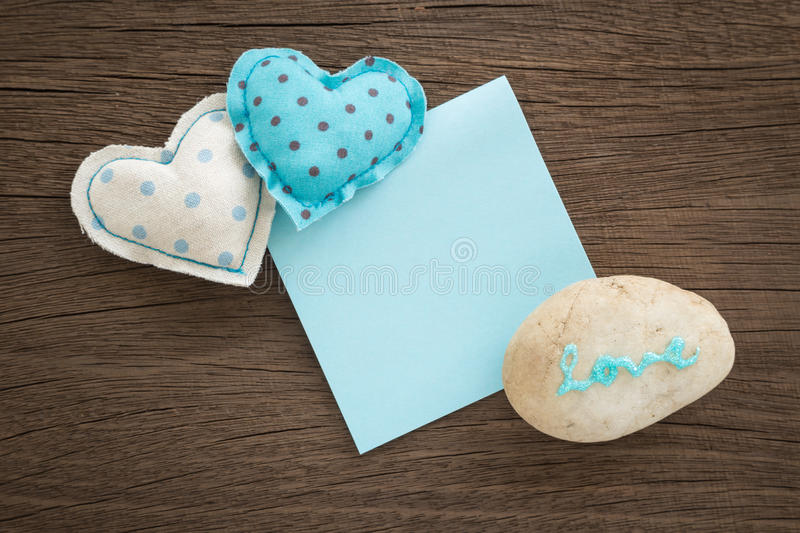 Sweet love hearts and blue blank paper on wood. Blue hearts handmade crafts from polka dot cotton cloth with love word on pebble and blank paper note place on stock photography