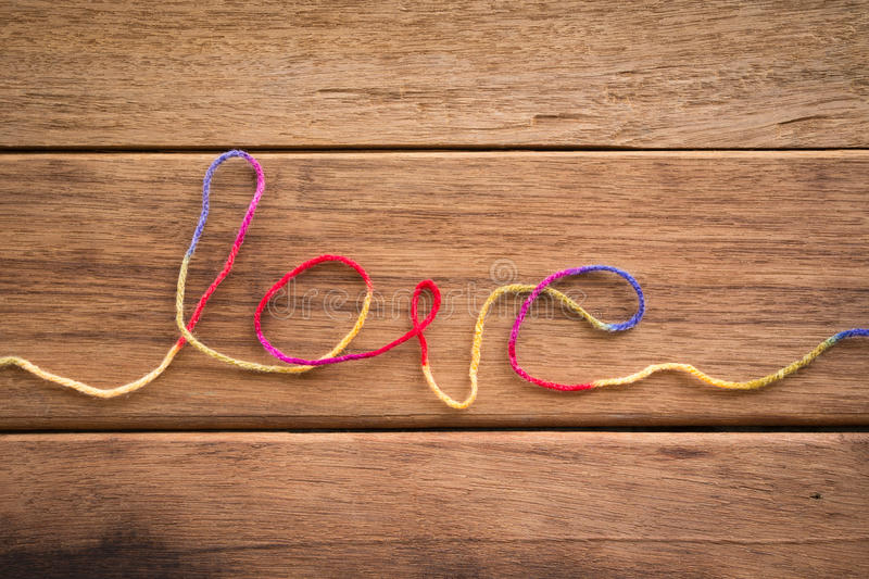 Sweet love word form yarn for wedding and valentine. Sweet love word from colorful yarn place on wood texture, wedding and valentine's day symbol stock images