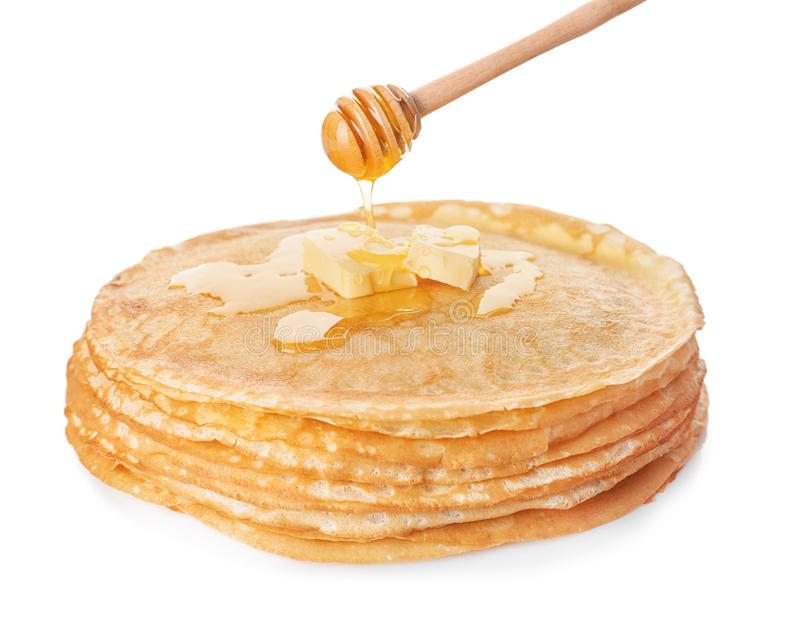 Sweet maple syrup dripping from dipper onto tasty thin pancakes royalty free stock image