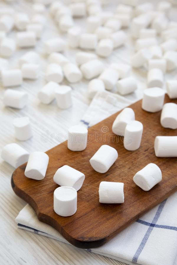 Sweet marshmallows on rustic wooden board over white wooden background. Heap of fluffy marshmallows. Side view. stock photos