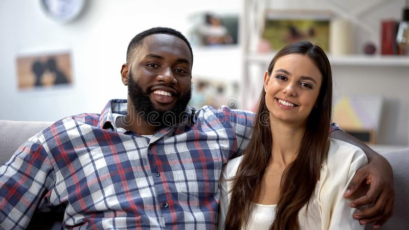 Sweet mixed-race couple hugging and looking at camera, spending time together stock images