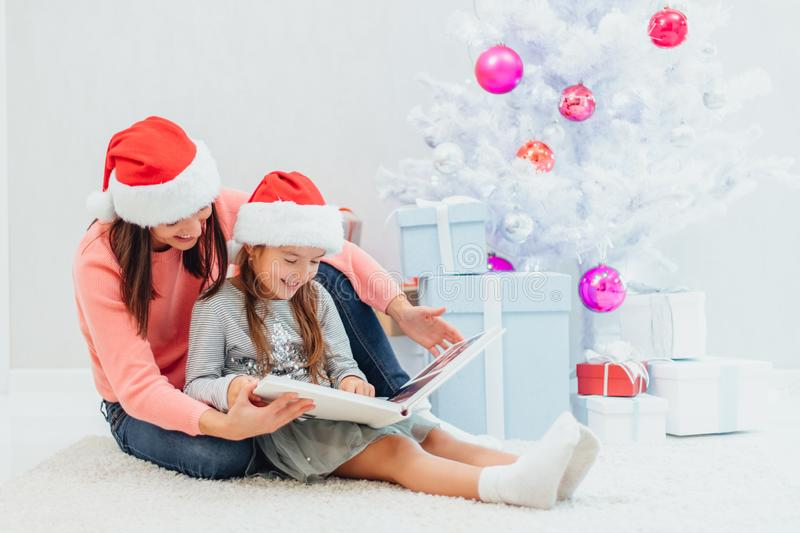 Sweet mother and daughter are looking through the family photo album, recollecting their good old memories on Christmas royalty free stock images