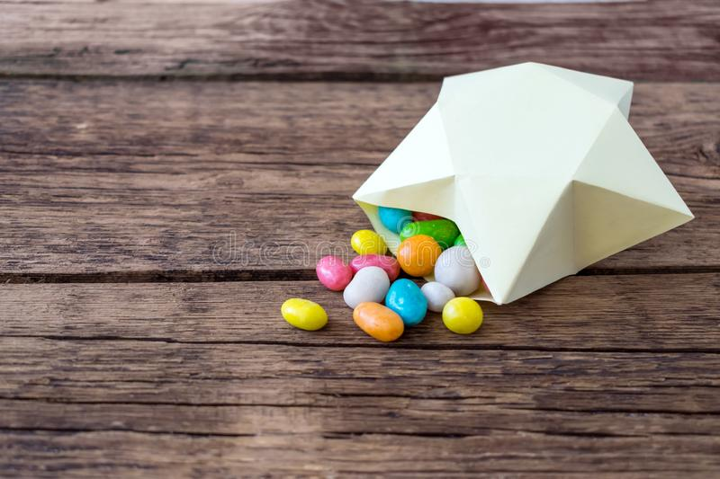 Sweet multicolored candy pills in paper gift box in the shape of royalty free stock image