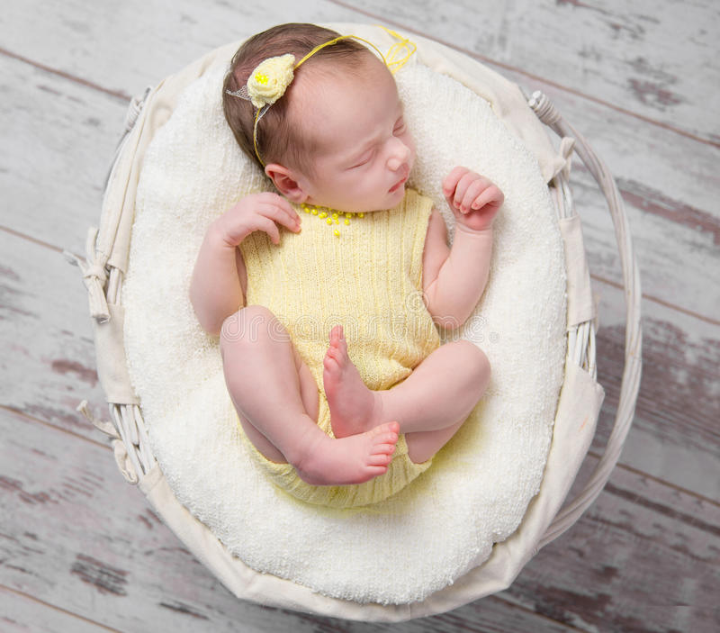 Sweet newborn girl in yellow sleeping in basket royalty free stock images