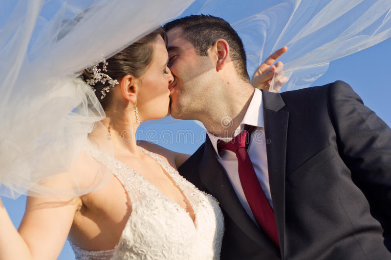 Sweet Newly Married Couple Kissing Outdoor. Close up Sweet Newly Married Couple Kissing Outdoor with Veil of Bride Flying in the Wind on Light Blue Sky stock photography