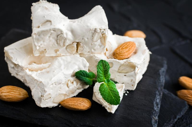 Sweet nougat with almonds. On black stone board on concrete background. Pieces of white nougat served on a stone plate royalty free stock images