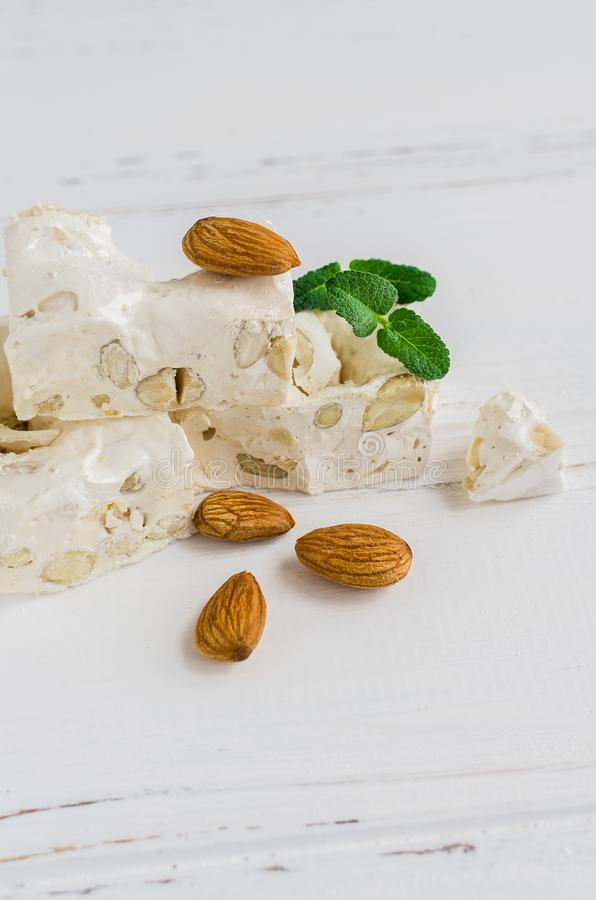 Sweet nougat with almonds. On white wooden background with place for text. Pieces of white nougat. Copy space stock photos