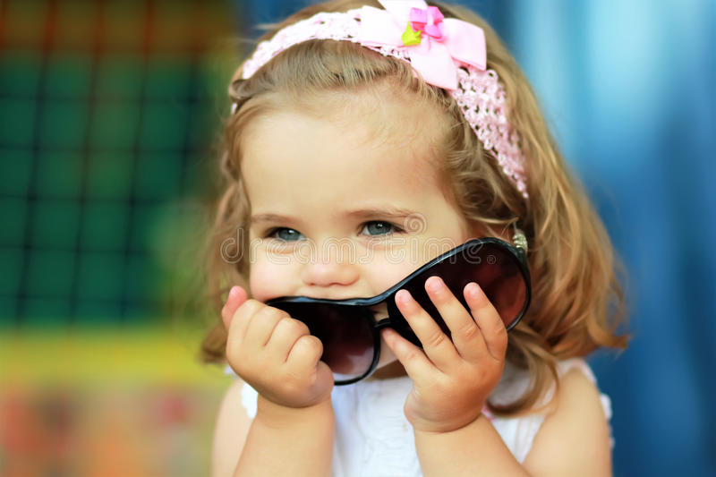 Sweet one year old girl who`s stolen mom`s sunglasses and happy to wear them trying to look like a grown up. Portrait of a sweet one year old girl who`s stolen royalty free stock photo