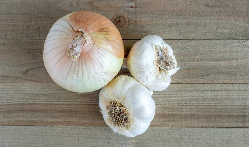 A sweet onion and 2 garlic bulbs on a wood background royalty free stock image