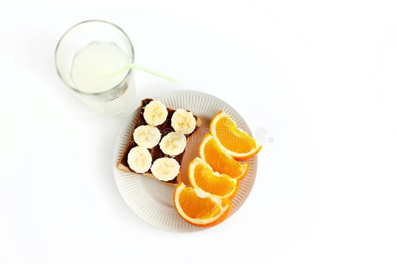 Sweet oranges and banana on bread with chocolate and fresh drink stock image
