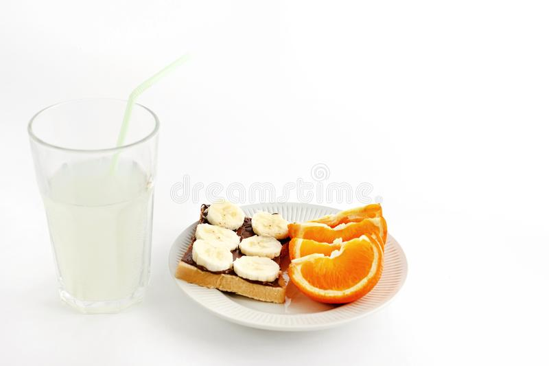 Sweet oranges and banana on bread with chocolate and fresh drink royalty free stock photo