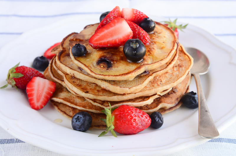 Sweet pancakes for breakfast. Pancakes with honey and berries royalty free stock photography