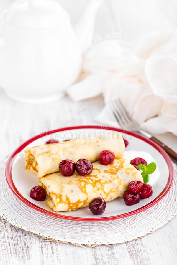 Sweet pancakes with cherry. On plate stock photos
