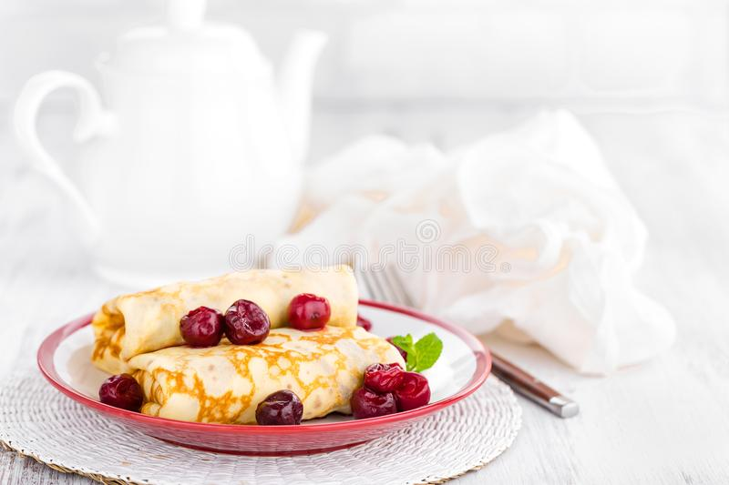 Sweet pancakes with cherry. On plate royalty free stock photo
